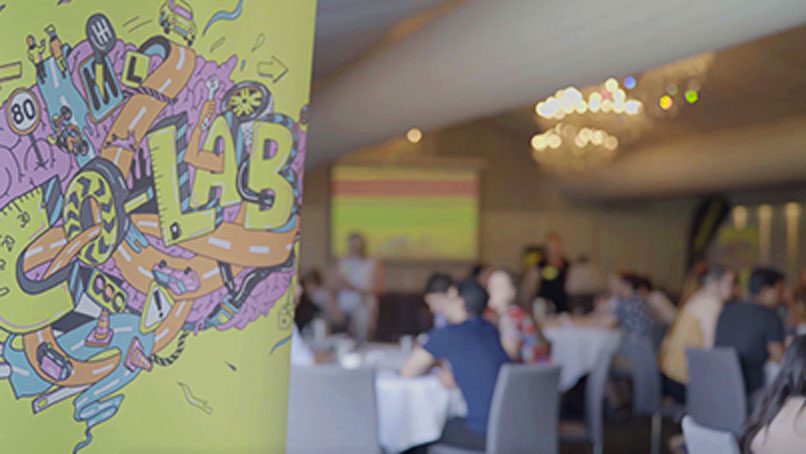 View of a conference room with a Co-Lab banner and people sitting in the background