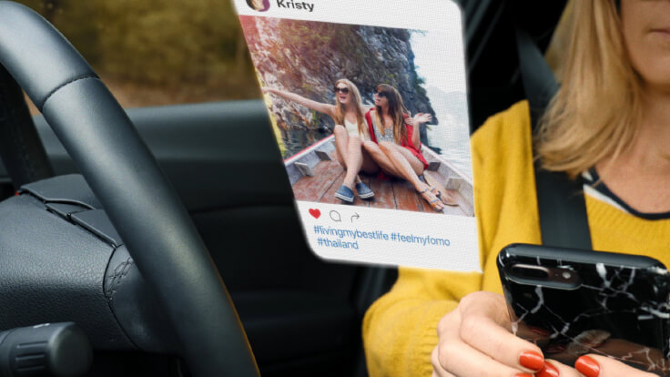 Female driver scrolling through Instagram on phone while driving