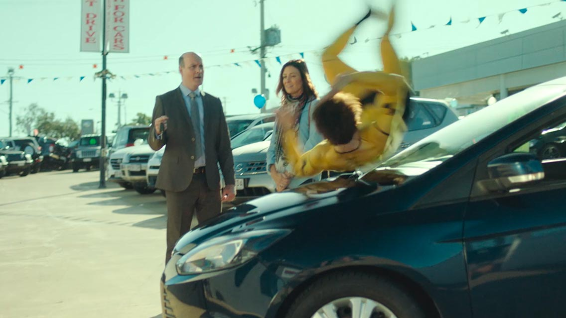 A young guy dressed like a crash dummy rolls across a car while a salesman watches in astonishment